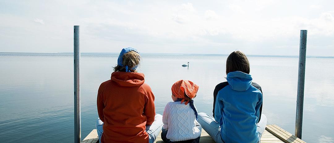 Ihmiset istuu laiturilla katsoen järvelle.