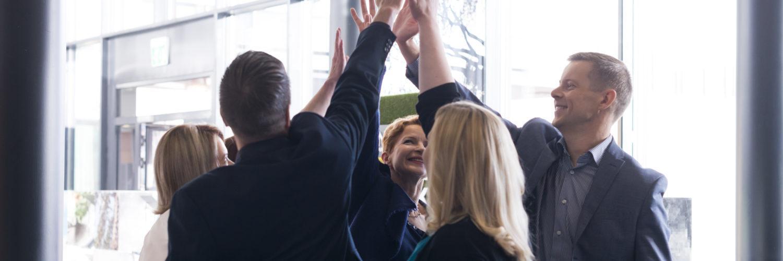 Ihmiset nostavat yhdessä kädet ilmaan.