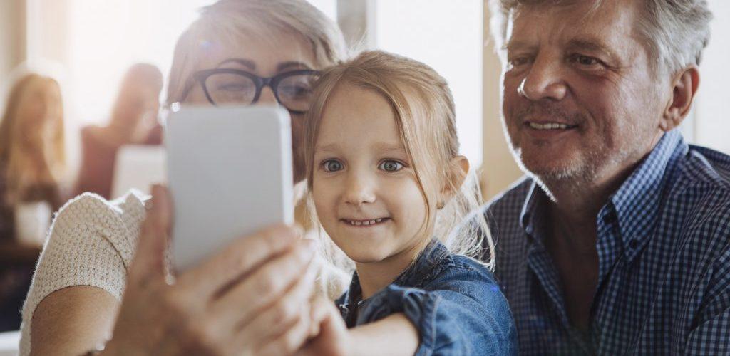 Mies, nainen ja lapsi katsovat puhelinta.