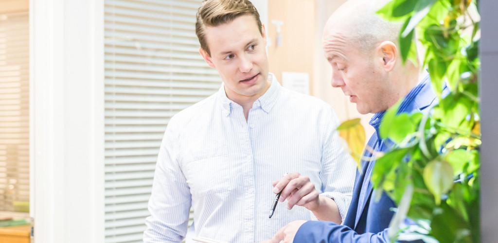 Miehet keskustelevat toimistossa tablet kädessä.
