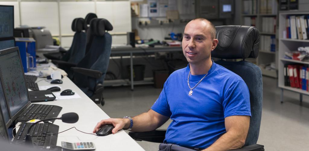Mies istuu työpöydän ääressä.