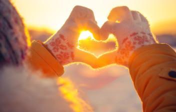 Käsin muodostettu sydän, josta paistaa auringonsäde.