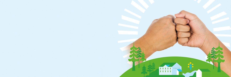 Kädet yhdessä ja alla luontoa sekä taloja