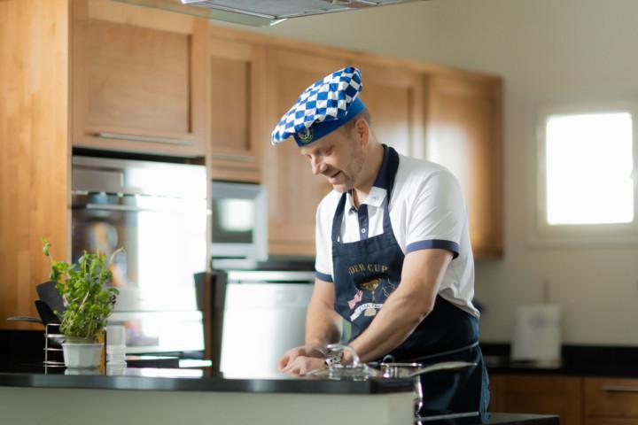 Mies kokkaa kokinhattu päässä.