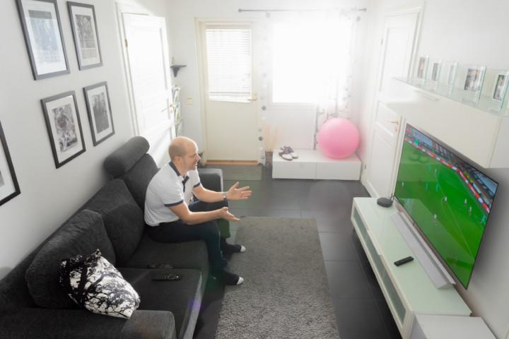 Mies katsoo televisiosta jalkapalloa.