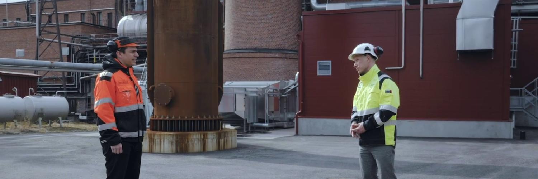 Miehet seisovat tehtaan edessä ja keskustelevat