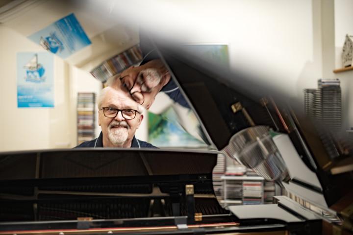 Musiikkineuvos, musiikinlehtori, Oulaisten Nuorisokuoron johtaja Tapani Tirilä, Oulainen, soittaa flyygeliä olohuoneessa.